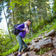Woman with backpack hiking into the forest - PhotoDune Item for Sale