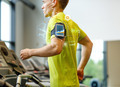 man with smartphone exercising on treadmill in gym - PhotoDune Item for Sale