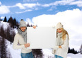 smiling couple in winter clothes with blank board - PhotoDune Item for Sale