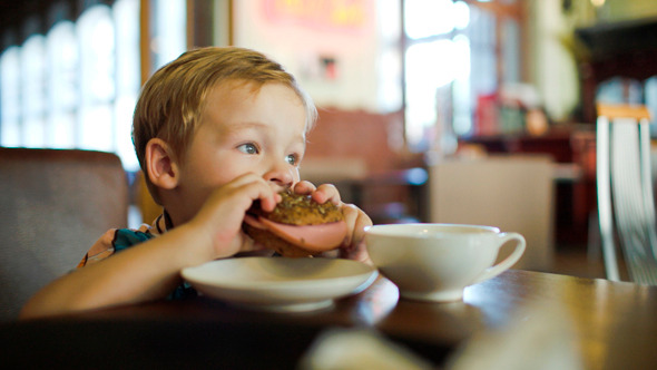 Little Boy Eating Sandwich In A Cafe