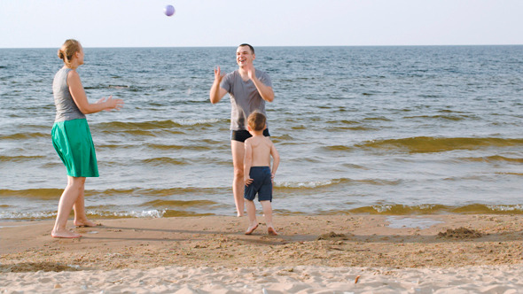 Parents And Child Playing Ball On The Beach