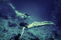 Two women synchronously swimming undersea - PhotoDune Item for Sale