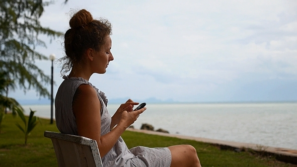 Woman Using Smart Phone at the Sea