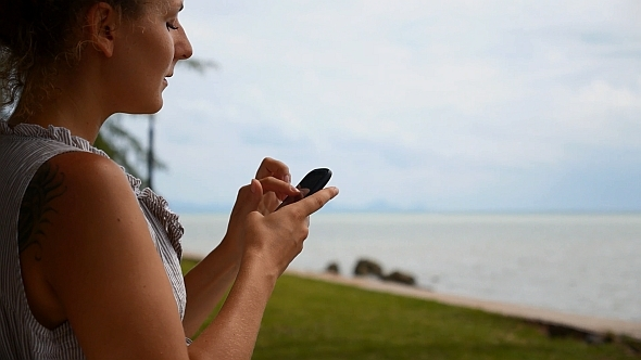 Woman with Smart Phone near the Sea