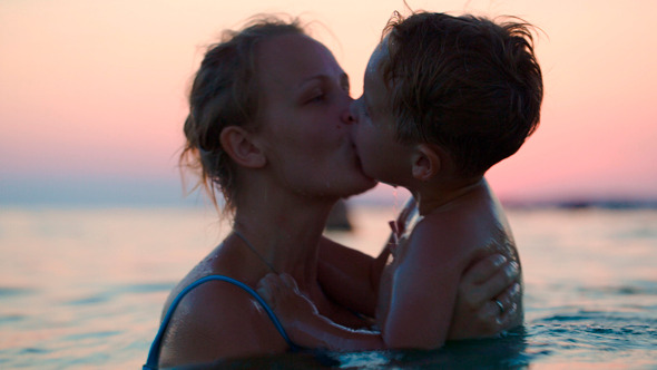 Mother And Son Having Fun In Sea At Sunset