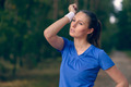 Woman athlete wiping sweat from her forehead - PhotoDune Item for Sale