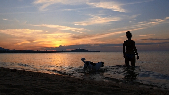 Woman with Dog in the Sea at Sunset