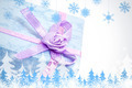 Snowflakes and fir trees against close up of blue gift box with purple ribbon