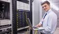 Smiling technician using laptop while analysing server in large data center