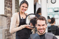 Pretty hair stylist showing man new haircut at the hair salon - PhotoDune Item for Sale