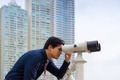 Asian business man with binoculars looking at city - PhotoDune Item for Sale