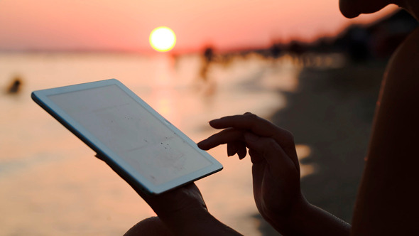 Girl Working With Tablet Pc On Beach At Sunset