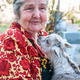 Senior woman holding a goatling on a background of his home - PhotoDune Item for Sale