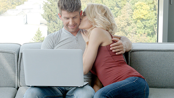 Young Couple Sitting On Couch With Laptop