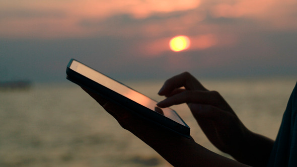Using Touchpad On The Beach At Sunset