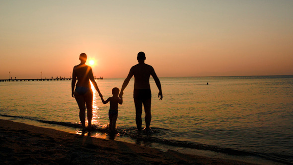 Parents And Child Bathing In The Sea At Sunset