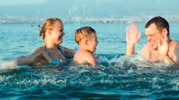 Happy Family Having Fun In Sea Water