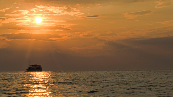 Sailing Ship In Quiet Sea At Sunset
