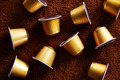Gold coffee capsules on coffee background - PhotoDune Item for Sale