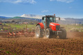 Brand new red tractor plowing the land - PhotoDune Item for Sale