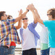 group of smiling friends making high five outdoors - PhotoDune Item for Sale