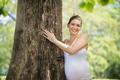 portrait pregnant mother woman hug tree park ecology - PhotoDune Item for Sale