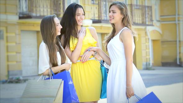 Three Happy Girls Discuss Their Shopping
