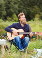 smiling man with guitar and dixie in camping - PhotoDune Item for Sale