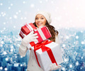 smiling young woman in santa helper hat with gifts - PhotoDune Item for Sale