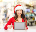 smiling woman in santa hat with gift and tablet pc - PhotoDune Item for Sale