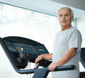 Tired senior man on a treadmill with bottle of water