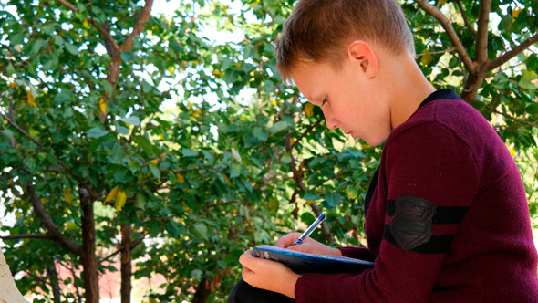 Boy Sitting On Bench Near Trees And Writing 4