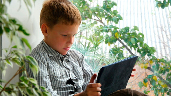 Boy Sitting By A Window Using His Tablet 1