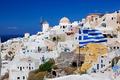Oia town on Santorini island, Greece. Waving Greek flag - PhotoDune Item for Sale