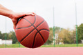 Young man on basketball court. Sitting and dribbling with ball - PhotoDune Item for Sale
