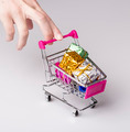 pink shopping cart in woman hand and blue gift - PhotoDune Item for Sale