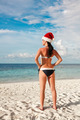 Woman in santa hat on the beach - PhotoDune Item for Sale