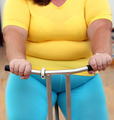 overweight woman exercising on bike simulator - PhotoDune Item for Sale