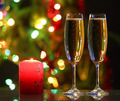 glasses with champagne and candle against festive lights - PhotoDune Item for Sale