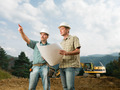 partners looking at blueprint on construction site - PhotoDune Item for Sale