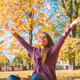 Happy young woman rejoicing in an autumn park - PhotoDune Item for Sale