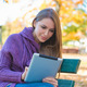 Young woman using her tablet in an autumn park - PhotoDune Item for Sale