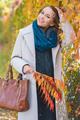 Stylish young woman picking autumn leaves - PhotoDune Item for Sale