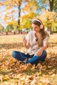 Young woman listening to music in an autumn park - PhotoDune Item for Sale