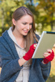 Smiling woman in red mittens using a tablet - PhotoDune Item for Sale