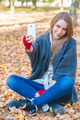 Smiling woman taking a selfie in an autumn park - PhotoDune Item for Sale