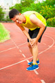 young male runner suffering from knee injury on the track in the stadium - PhotoDune Item for Sale