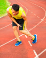young male runner suffering from leg cramp on the track in the stadium - PhotoDune Item for Sale