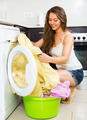 Pretty young woman washing clothes in washer - PhotoDune Item for Sale
