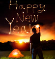 young man drawing happy new year words by sparkling stick. camping on the mountain - PhotoDune Item for Sale